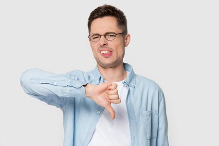 Unzufriedene kaukasische männliche Kunden in Brille und Hemd einzeln auf grauem Studiohintergrund zeigen Daumen nach unten, unglücklicher junger Mann in Brillen mag keinen Service, keine Empfehlung oder Beratung