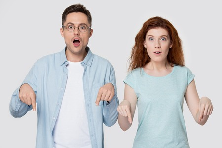 Surprised young man and woman in casual clothes isolated on grey studio background point downward with fingers, shocked couple show down indicating place for ad or good sale offer or deal