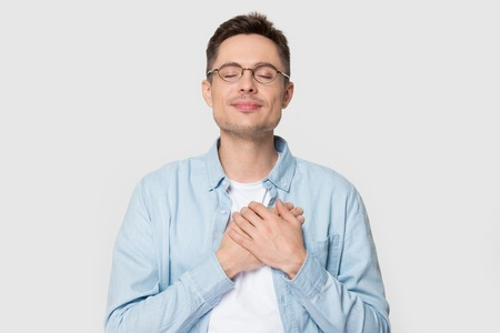 Calm young Caucasian male in glasses isolated on grey studio background hold hands on chest close to heart feel grateful, thankful European man in appreciation thanking fate. Gratitude concept Stockfoto