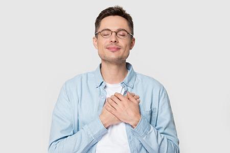 Ruhiger junger kaukasischer Mann in Gläsern, isoliert auf grauem Studiohintergrund, halten die Hände auf der Brust nah am Herzen, fühlen sich dankbar, dankbarer europäischer Mann in Anerkennung, der dem Schicksal dankt. Dankbarkeitskonzept