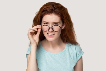 Doubtful red-haired young woman take off glasses look at camera not believing something, unsure redhead girl in eyewear isolated on grey background feel dubious or hesitant, wondering on idea