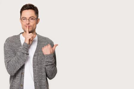 L'uomo caucasico millenario con gli occhiali mostra con il dito nero copia spazio per la pubblicità, fa un gesto di silenzio, giovane maschio isolato su sfondo grigio studio punto in vendita, fa segno di zitto tranquillo, dice segreto