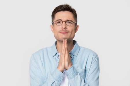 Hopeful millennial Caucasian man in glasses join hands in prayer thanking asking for best, young European male wearing spectacles isolated on grey studio background pray hoping. Faith concept Stock Photo