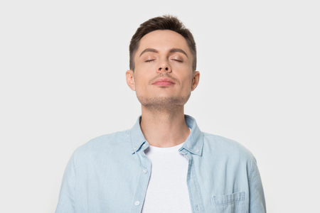 Calm young Caucasian male isolated on grey studio background enjoy pleasant smell or fragrance, relaxed European man in shirt breath deep, feel mindful inhaling fresh air. Stress free concept Stock Photo - 121257060