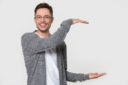 Smiling millennial Caucasian man wear glasses show big size with both hands, happy European male in spectacles isolated on grey studio background demonstrate large space or holding object, copy space