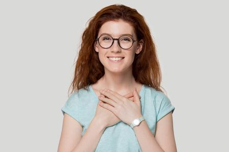 Une jeune femme rousse heureuse et reconnaissante dans des lunettes rondes tient la main sur la poitrine près du cœur, se sentant reconnaissante et touchée, souriante et pleine d'espoir, une fille rousse isolée sur fond gris montre une foi sincère