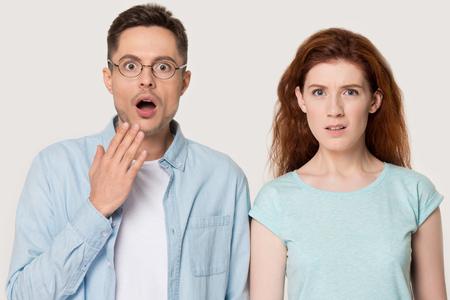 Schockiertes tausendjähriges Paar einzeln auf grauem Studiohintergrund bedecken den Mund, der das unerwartete Ding verzieht, überraschter junger Mann und Frau, die von unglaublichem Ereignis oder Geschehen überrascht sind