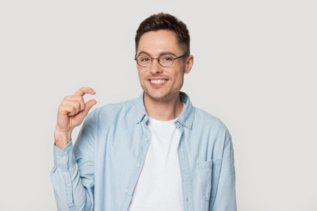 Smiling positive Caucasian man in glasses show small size by fingers, happy European male in spectacles isolated on grey studio background demonstrate tiny measure, tell about little decreased prices