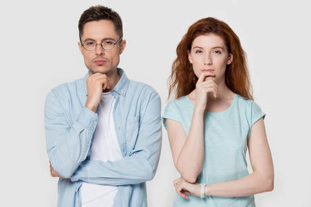 Pensive millennial couple stand isolated on grey studio background touch chin with finger thinking of something, thoughtful man and woman consider or plan idea, look at camera lost in thoughts Stock Photo