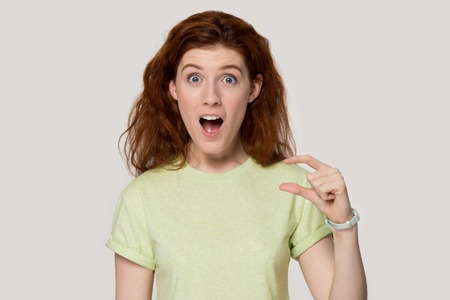 Amazed red-haired young woman isolated on grey studio background show little tiny size by fingers, surprised redhead nerd student girl in t-shirt gesture measurement tell about small prices or rates