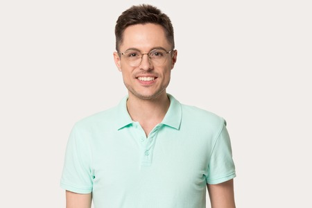 Headshot portrait of smiling millennial Caucasian man wearing glasses isolated on grey studio background, happy male in polo t-shirt and spectacles standing looking posing at camera Stock Photo