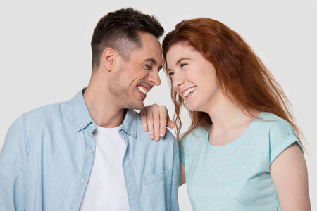 Happy millennial man and woman laugh at funny joke have fun spend time together, smiling young couple or family isolated on grey studio background touch foreheads enjoy tender pleasant moment Standard-Bild