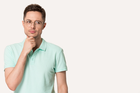 Pensive caucasian young man in glasses thinking or considering idea, looking at free copy space aside, thoughtful millennial male client isolated on grey studio background touch chin making decision Stock Photo