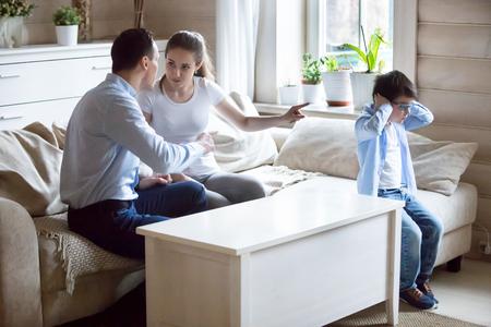 Frustrierter kleiner Junge bedeckt die Ohren, um nicht zu hören, dass sich die Eltern streiten. Der verängstigte Sohn sorgt sich um den Konflikt zwischen Mutter und Vater, schreit, zeigt auf die Tür. Familienprobleme, Scheidung von Ehepaaren, schlechtes Beziehungskonzept
