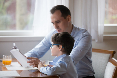 Father reading book to son aloud at kitchen at home. Daddy help boy to study on weekend, teaching, reading story, fairy tale together. Happy family spending time together, leisure time concept Stock Photo
