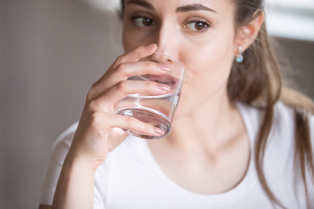 Close up top view woman drinking clear water from glass. Millennial beautiful female taking pill, tablet, medication, refilling water balance. Thirsty, dehydration, healthcare, medical concept