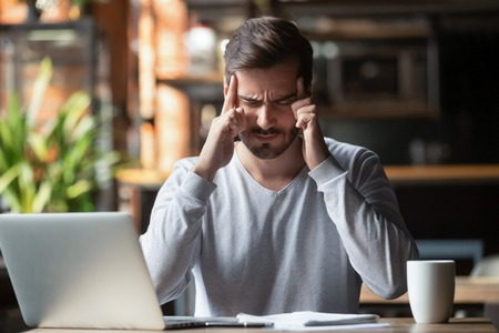 Man sitting at table near pc closed eyes touching forehead with fingers make en effort thinking, suffering from headache. Search important decision or high pressure painful feelings discomfort concept