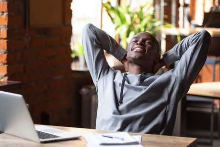African happy businessman or student guy sitting at table putting hands behind head closed eyes feels satisfaction after finish learning. Stress relief, successful good results, completed work concept Stock fotó