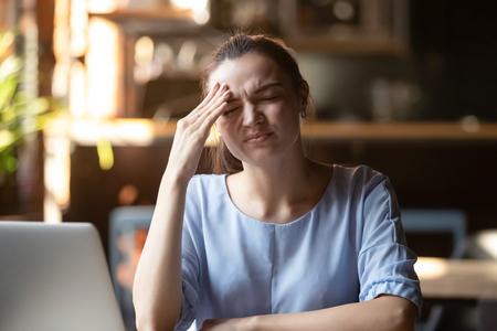 Geschäftsfrau oder Studentin, die am Tisch in der Nähe des PCs sitzt, fühlt sich gestresst, verwirrte Gesichtsausdrücke, hat Kopfschmerzen, hat wichtige Dinge vergessen, einen Termin verpasst, einen Fehler im Arbeits- oder Studienkonzept gemacht