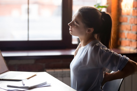 Side view young woman sitting at table working using computer take break touching massaging lower back feels discomfort after long sedentary studying, poor posture, incorrect stooped position concept