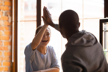 Different ethnicity heterosexual friends teammates gather in cafe having chance meeting in public place give high five buddies gesture as handshake. Greeting, celebrate congratulate great news concept Stock Photo