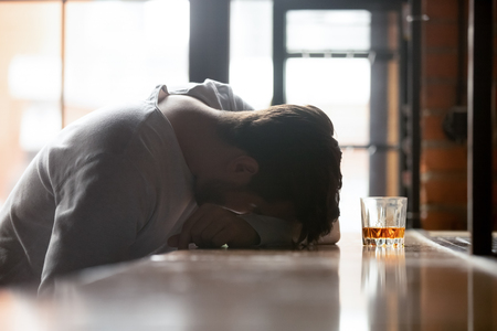 Drunk boozy man sleeping lying on bar counter after drinking large amount of alcoholic beverage glass of whiskey strong booze near him, concept of alcohol use disorder AUD alcoholism health problems Imagens