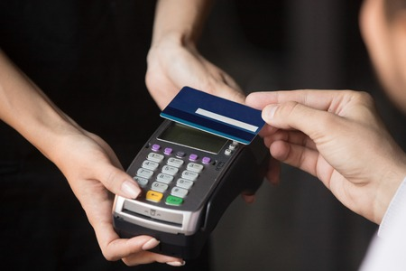 Customer pay bill in cafeteria or restaurant with contactless credit debit card NFC technology waiter use reader machine, top close up hands client and cashier, easy smart fast cashless tech concept