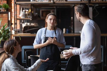 La pareja de clientes de restaurante enojados hostiles o amigos que hablan con el personal de espera en un lugar público se quejan del servicio prolongado de café frío, la camarera de platos malcriados se siente culpable por el concepto de pedidos mixtos
