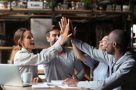 Friends university students sitting together at table full of study materials textbooks giving high five, multiracial associates colleagues feel happy succeed goal great result learning finish concept
