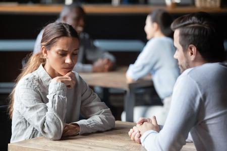 Schüchterne oder gelangweilte gemischtrassige Frau, die während des Speed-Datings am Tisch im Café sitzt, gleichgültig gegenüber dem in Gedanken versunkenen Gespräch, erfolglose erste Bekanntschaft, unglückliches Versagen des romantischen Date-Konzepts