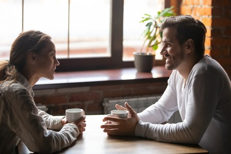 Side view smiling biracial woman sitting at table in cafe with caucasian man couple talking in cozy coffeeshop drinking tea coffee. Heterosexual friends romantic relationships or speed dating concept