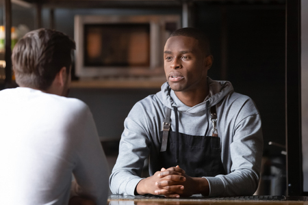 Serious diverse males talking inside cafe, african chef interviewing the candidate for position at restaurant kitchen, restaurateur business owner negotiating with grocery supplier or partner concept