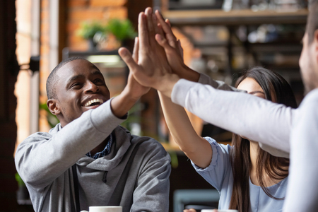 Laughing friends sitting in cafe spends time together feels happy giving high five hand gesture. Concept of equality and friendships of different ethnicity millennial people, unity warm relationships