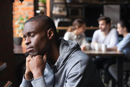 Der frustrierte traurige Afroamerikaner, der allein in der Cafeteria sitzt, fühlt sich einsam, dass die Menschen die Kommunikation mit ihm aufgrund seiner Hautfarbe vermeiden, ein unglücklicher Ausgestoßener leidet unter dem Konzept der Rassendiskriminierung