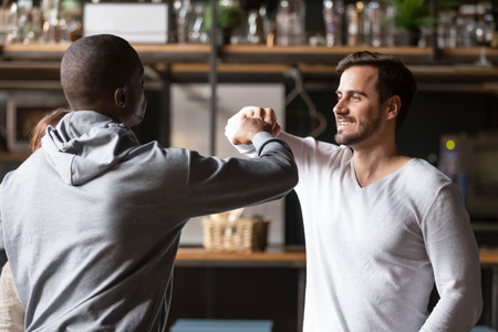 Cheerful diverse friends gathered in cafe or bar greeting each other feels happy, african and caucasian guys fist bumping nice to meet concept, showing respect and friendship having good relationships Imagens