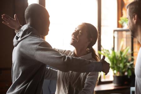 Divers amis se sont réunis à la cafétéria, une femme biraciale embrasse un homme africain heureux de se voir. Relations chaleureuses, amitié ethnique différente, rencontre fortuite et concept de soutien