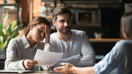Biracial woman sitting with mates at table in cafe holding documents feels unsatisfied accusing colleague mistake in report, inattentive work, unsuccessful result, accusation and justification concept