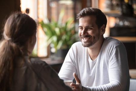Vista trasera de la mujer sentada a la mesa en el café con un hombre guapo y sonriente, la gente pasa tiempo en la reunión en busca de un alma gemela, el hombre habla de sí mismo dando una buena primera impresión, concepto de citas rápidas Foto de archivo