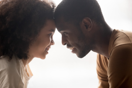 Close up profile african father and cute daughter faces touch foreheads looking in eyes each other feels love understanding, enjoy tender moment, bonding connection care and warm relationships concept Archivio Fotografico