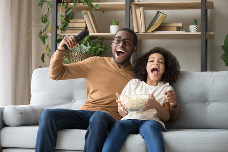 Overjoyed black family sitting on sofa watch football sport tv game feels happy excited celebrating cheering soccer victory last minute goal dad kid eating popcorn enjoy time at home together concept.