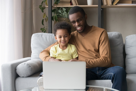 Smiling black dad hug little son sitting on sofa in living room at home spends time together watching cartoons educational program online on pc, weekend leisure activities wireless tech usage concept Archivio Fotografico