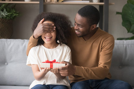 Happy african loving father covering eyes with hand prepare for preschool daughter gift box surprise, family sitting in living room at home celebrating life event, happy birthday, best wishes concept