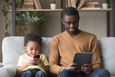 African father in glasses holds tablet read media spend free time with little adorable son, kid use smartphone watching cartoons educational videos online play game, addicted of gadgets family concept