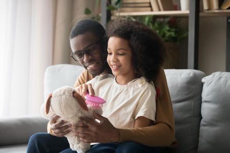 Mixed race schoolgirl daughter sitting on black daddy lap combing stuffed toy dog play together rest on couch living room at home, teach care for others, concept of leisure activity games with child