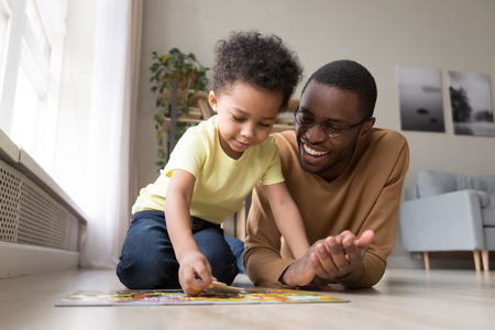 Papá negro, hijo pequeño, recoger rompecabezas, juntar piezas en un piso cálido en la sala de estar. La actividad de ocio se divierte en casa, la capacidad de razonamiento lógico, desarrolla el concepto de habilidad de resolución y motricidad fina Foto de archivo