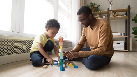 Smiling father spend free time with preschool adorable son african family sitting on warm heated wooden floor in playroom at home play with toy blocks colourful set building a tower having fun concept.