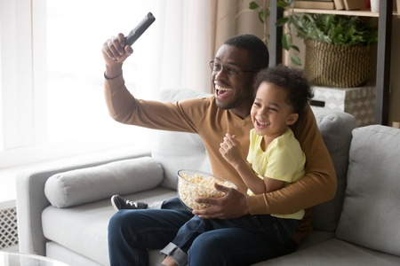 Excited african father raise hand hold remote control celebrate football team victory little son sitting on dad lap family eating popcorn watching sport program on tv, leisure activity at home concept