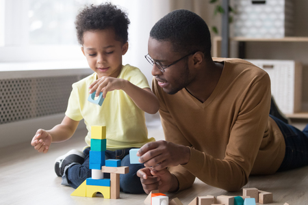 Little african boy building tower use colourful toy blocks set sitting on wooden warm heated floor in playroom with daddy or babysitter man, educational game, family at home leisure activities concept Stock Photo