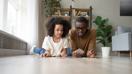 Black dad daughter school age assemble jigsaw puzzle put together pieces lying on warm heated floor in living room. Leisure hobby having fun, logical reasoning ability, develop solving skills concept Reklamní fotografie