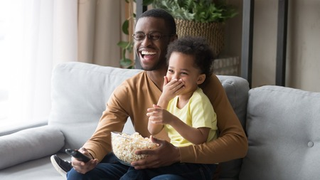 Family sitting on couch in living room spending weekend together at home, african father holding on lap little son using remote control watching funny movie comedy laughing having fun eating popcorn